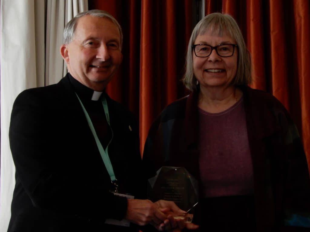 Anne Klejment accepts her award from ACHA president Richard Gribble, C.S.C.