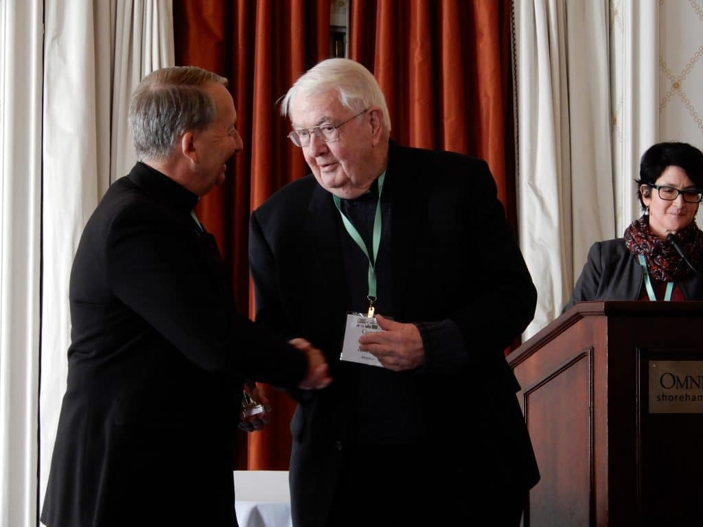 Gerald P. Fogarty, S.J. (right), is congratulated by ACHA president Richard Gribble, C.S.C.