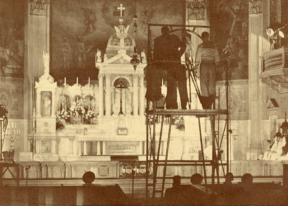 "A photograph of the main altar at Our Lady of Sorrows with stands erected for camera men filming the Solemn High Mass. Photo from ""Souvenir Program The Eternal Gift""."